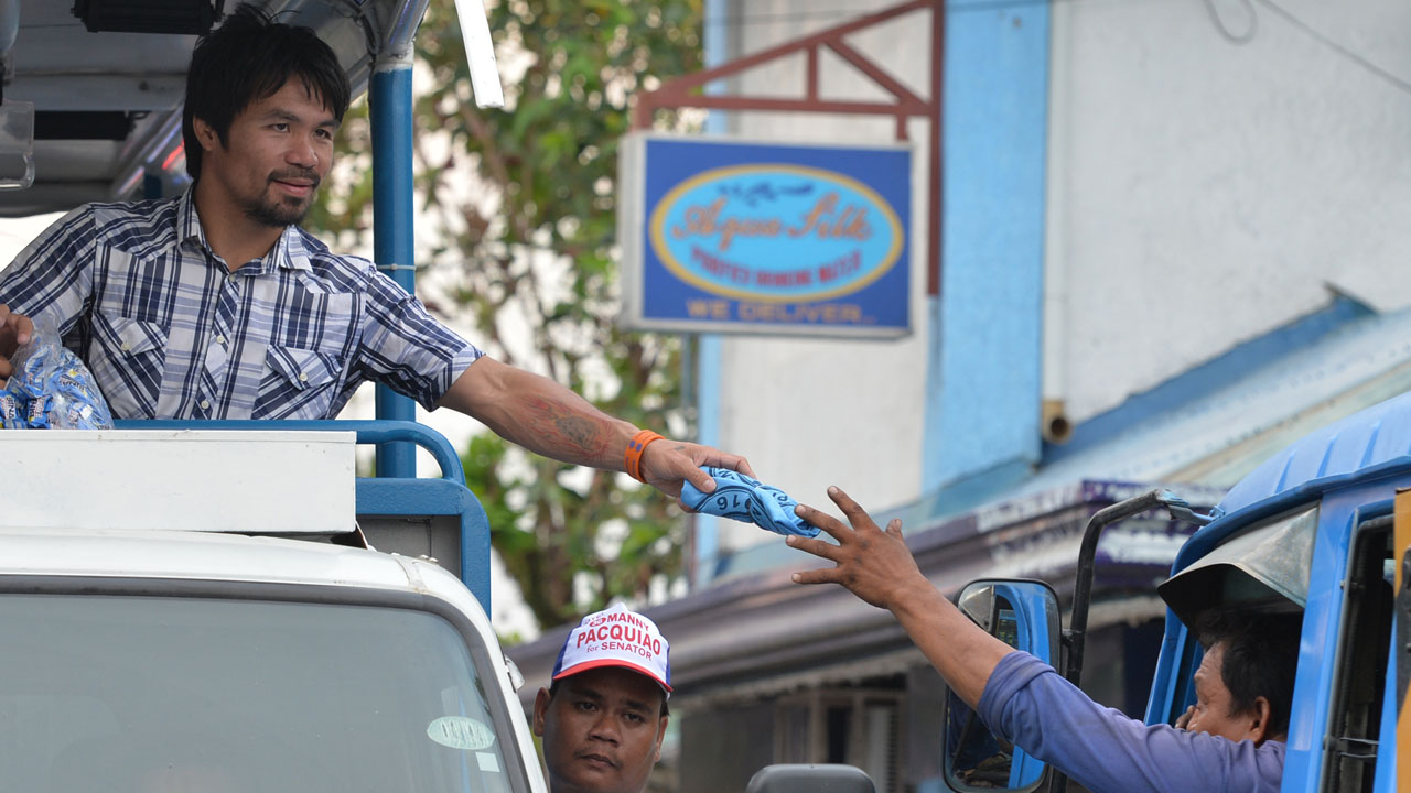 In this picture taken on April 28, 2016, Philippine boxing legend Manny Pacquiao gives a t-shirt to a supporter during a campaign sortie in Calamba town, Laguna province, south of Manila. Pacquiao smiles as he soaks up the sounds of adoring fans screaming his name, their cheers heralding a new career as one of the Philippines' most powerful politicians. / AFP PHOTO / TED ALJIBE / To go with AFP story Philippines-vote-Pacquiao-Box by Ayee Macaraig