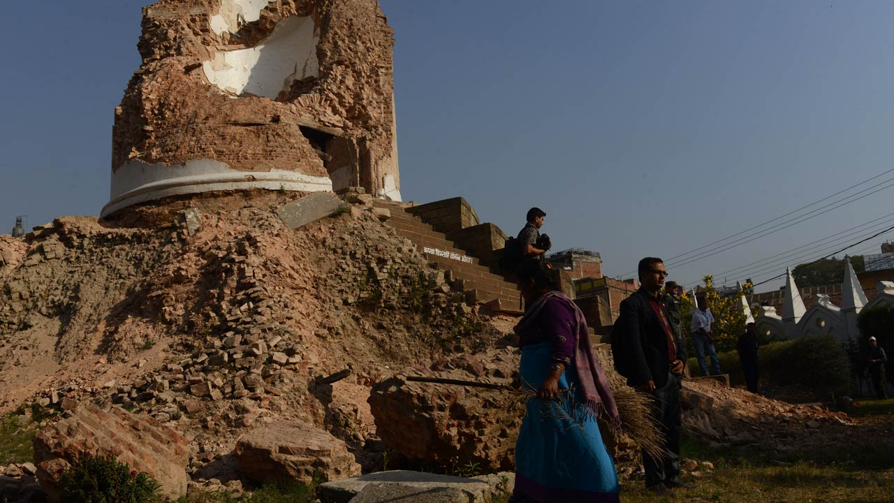 Nepalese women clean the Darahara monument that was destroyed in the 2015 earthquake, in Kathmandu on April 24, 2016. Nepal held memorial services on April 24 for the thousands killed in a massive earthquake one year ago, as victims still living in tents accused the government of failing them. PRAKASH MATHEMA / AFP