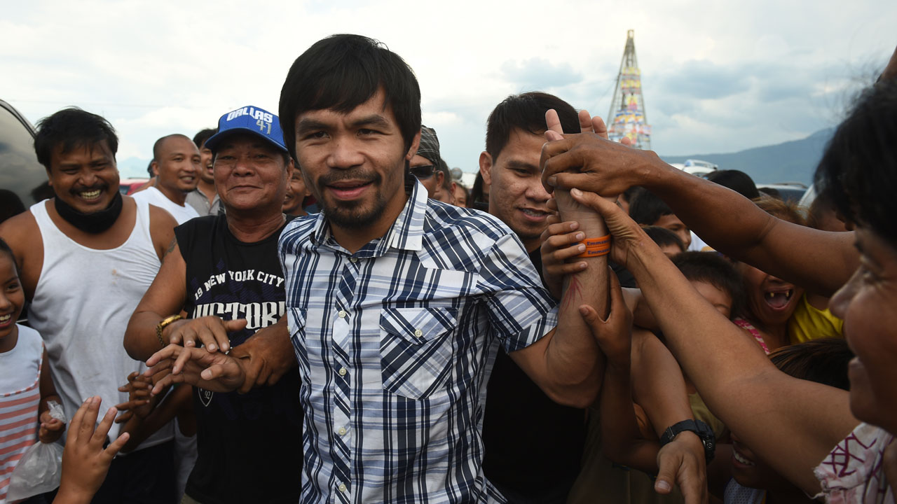 Philippine boxing icon Manny Pacquiao is mobbed bu supporters during a campaign sortie in Calamba town, Laguna province south of Manila on April 28, 2016.   Pacquiao expressed shock on April 28 at President Benigno Aquino's claim that Islamic militants planned to kidnap him, and said the alleged plot should not have been made public. / AFP PHOTO / TED ALJIBE