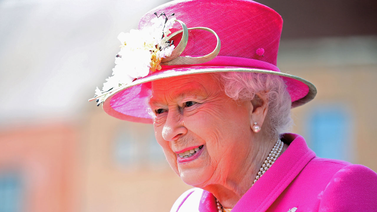 Britain's Queen Elizabeth II reacts as she tours the Royal Mail Windsor postal delivery office in Windsor, west of London, on April 20, 2016, to mark the 500th anniversary of the Postal Service. Queen Elizabeth II is set to celebrate her 90th birthday on April 21, with a family gathering and a cake baked by a reality television star, as a new poll finds Britain's longest serving monarch is as popular as ever. The queen has reigned for more than 63 years and shows no sign of retiring, even if she has in recent years passed on some of her duties to the younger royals. / AFP PHOTO / POOL / Chris Jackson