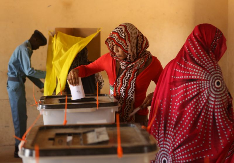 A Sudanese police officer stands at a polling booth as an electoral officer helps a woman cast her vote in the country's elections at a polling station in a classroom in Khartoum's southern suburb of Mayo on April 14, 2015 (AFP Photo/Patrick Baz)