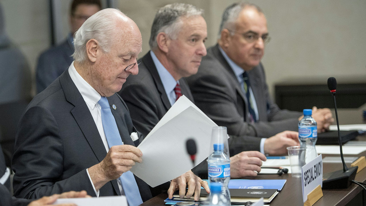 UN Special Envoy of the Secretary-General for Syria Staffan de Mistura (L) is seen seated prior a round of negotiations between the Syria's regime-tolerated opposition and the U.N., at the European headquarters of the United Nations in Geneva, on April 27, 2016. Russia has asked the United Nations to blacklist a major rebel group that is playing a key role in peace talks to end the Syrian civil war, its ambassador to the UN said. Mohammed Alloush, a leading figure in Jaish al-Islam (Army of Islam), is the chief negotiator for the High Negotiations Committee, the war-torn country's main opposition group, at UN-brokered peace talks in Geneva. / AFP PHOTO / POOL / MARTIAL TREZZINI