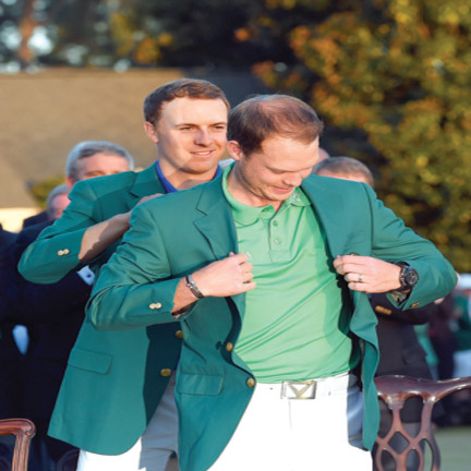 Jordan Spieth of the United States presents Danny Willett of England with the green jacket after Willett won the final round of the 2016 Masters Tournament at Augusta National Golf Club… on Sunday. PHOTO: AFP.