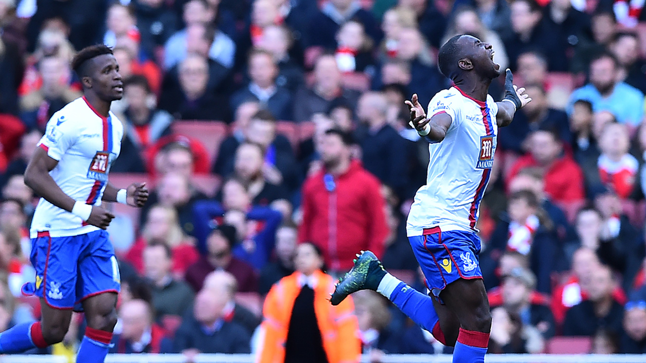 Crystal Palace's French-born Congolese midfielder Yannick Bolasie (R) celebrates scoring his team's first goal during the English Premier League football match between Arsenal and Crystal Palace at the Emirates Stadium in London on April 17, 2016. / AFP PHOTO / BEN STANSALL