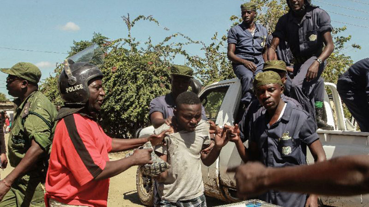 Zambian police apprehend a man in Lusaka where residents have attacked and looted foreign-run shops, on April 19, 2016 (AFP Photo/Salim Dawood)