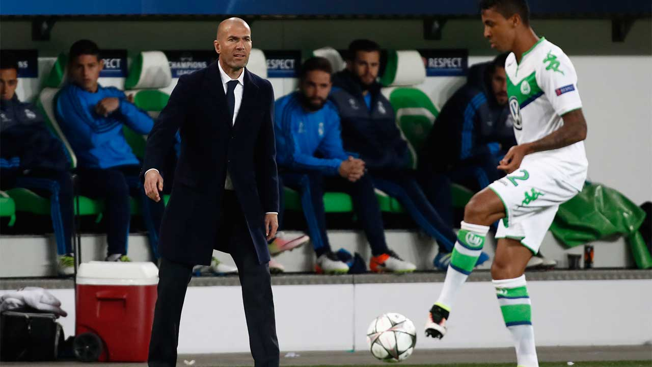 Real Madrid's French coach Zinedine Zidane (L) looks on as Wolfsburg's Brazilian midfielder Luiz Gustavo controls the ball