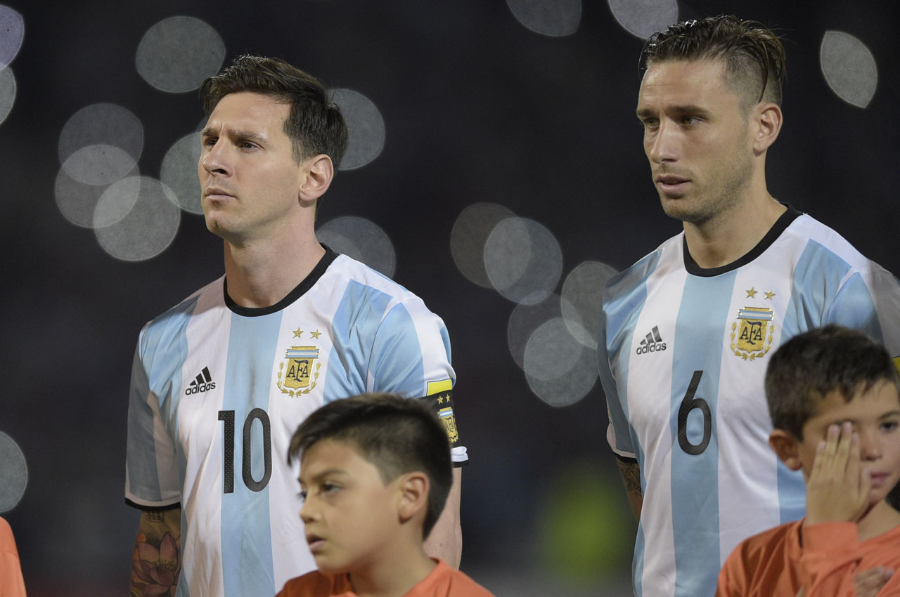 Argentina's Lionel Messi (L) and Argentina's Lucas Biglia listen to the national anthem before their Russia 2018 FIFA World Cup South American Qualifiers' football match against Bolivia in Cordoba, Argentina, on March 29, 2016.        AFP PHOTO / EITAN ABRAMOVICH / AFP PHOTO / EITAN ABRAMOVICH
