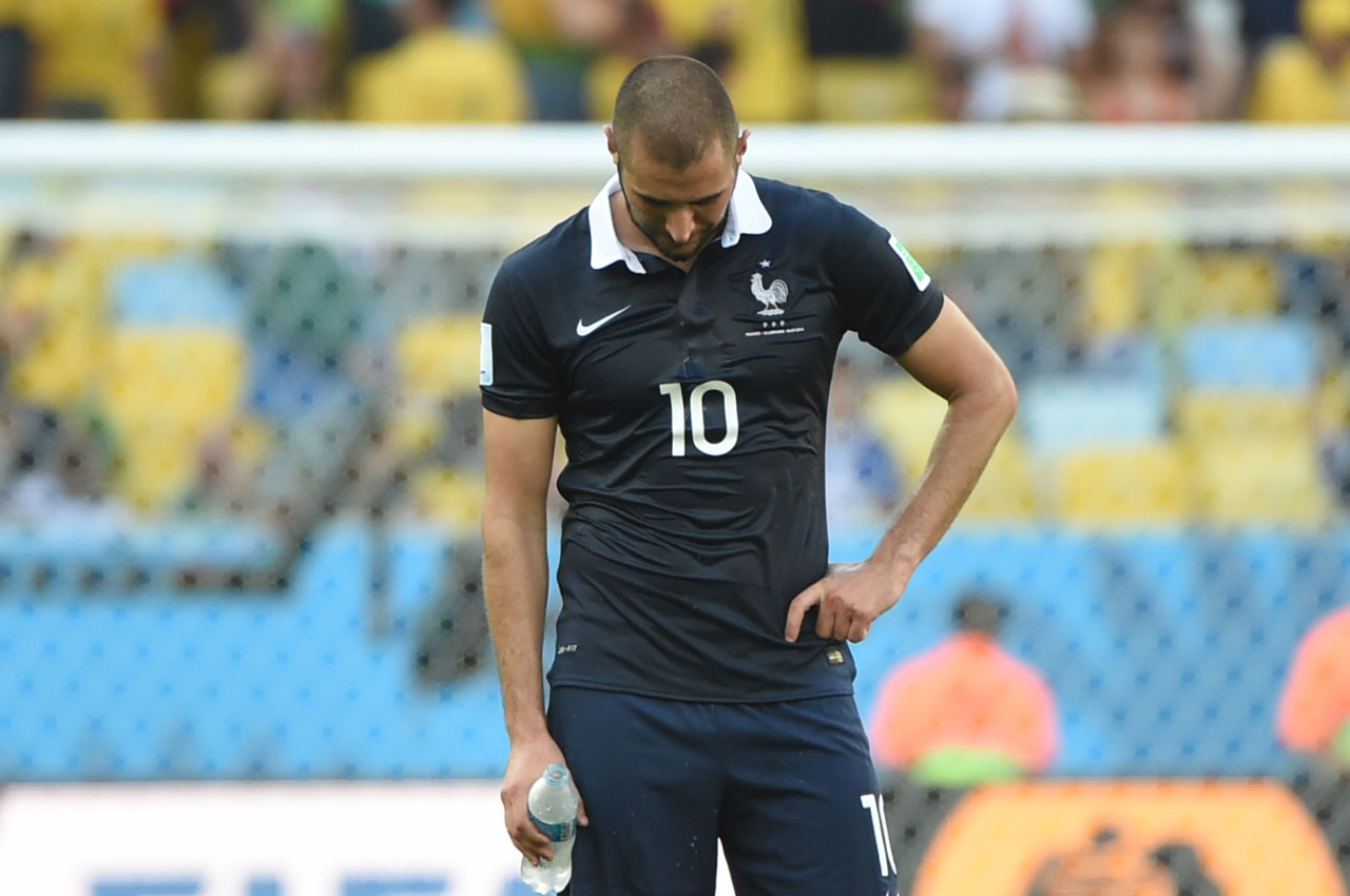 (FILES) This file photo taken on July 04, 2014 shows France's forward Karim Benzema (R) reacting at the end of the quarter-final football match between France and Germany at The Maracana Stadium in Rio de Janeiro. Embroiled in the Mathieu Valbuena sex-tape scandal, France forward Karim Benzema revealed on Twitter on April 13, 2016 that he will not be selected for Euro 2016. The French Football Federation (FFF) confirmed the news a short while after, with Real Madrid star Benzema to be left out after he was implicated in a sex-tape blackmail case that targeted his international teammate Valbuena. / AFP PHOTO / PATRIK STOLLARZ