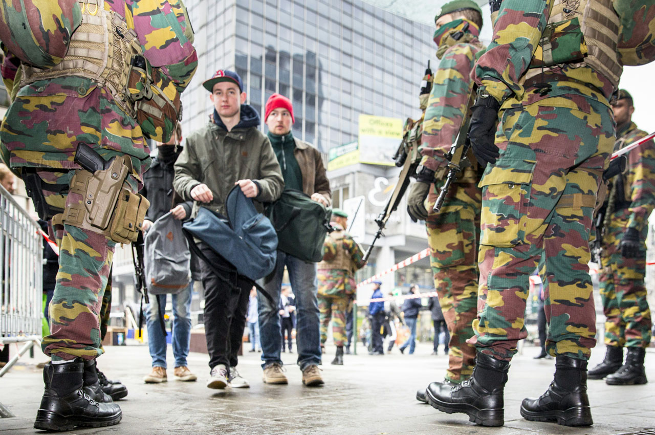 Soldiers control passers by in Brussels, on March 23 2016, one day after the attacks on Brussels airport and at a metro station.  About 20 people were killed on the metro and 14 at the airport in the rush-hour assaults, which came just days after the arrest in Brussels of the main fugitive suspect in November's gun and bomb rampage in Paris.  / AFP PHOTO / BELGA / HATIM KAGHAT / Belgium OUT