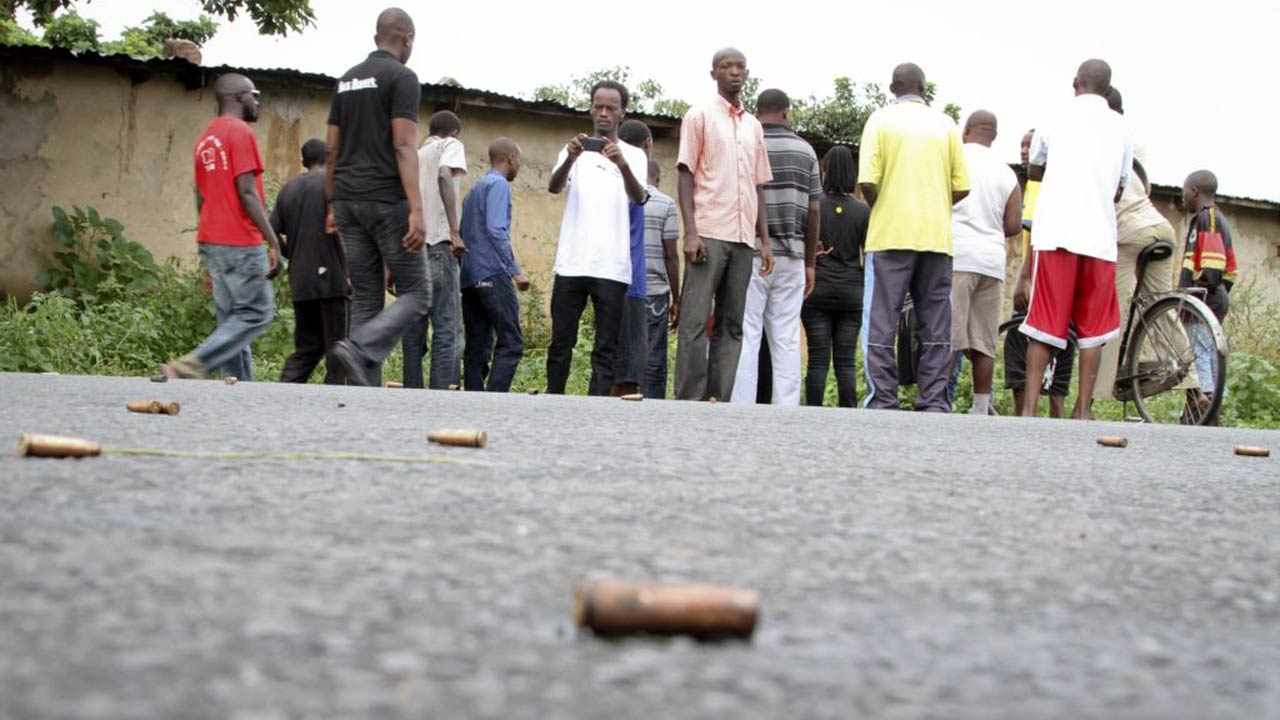 A man takes a picture of spent bullet casings lying on a street in the Nyakabiga neighbourhood of Bujumbura, Burundi. Burundi erupted into protests and violence in April 2015 after President Pierre Nkurunziza sought what many viewed as an unconstitutional third term. PHOTO: VOA