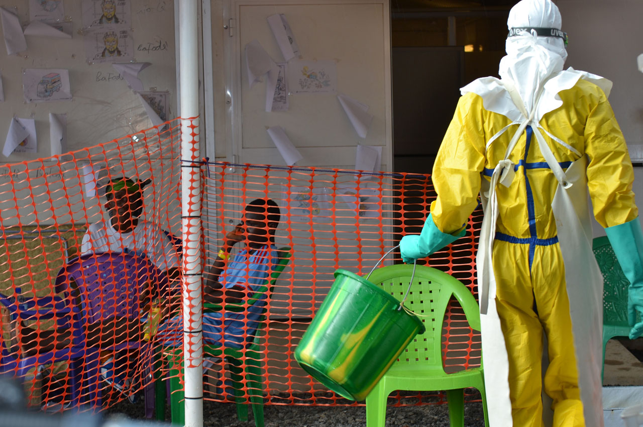 (FILES) This file photo taken on August 19, 2015 shows a health worker walking towards patients under quarantine at the Nongo ebola treatment centre in Conakry, Guinea on August 21, 2015.  A resurgence of Ebola in a rural Guinean community has killed seven people, health officials said on March 30, 2016, even as the World Health Organization voiced confidence that remaining isolated cases could be contained. / AFP / CELLOU BINANI