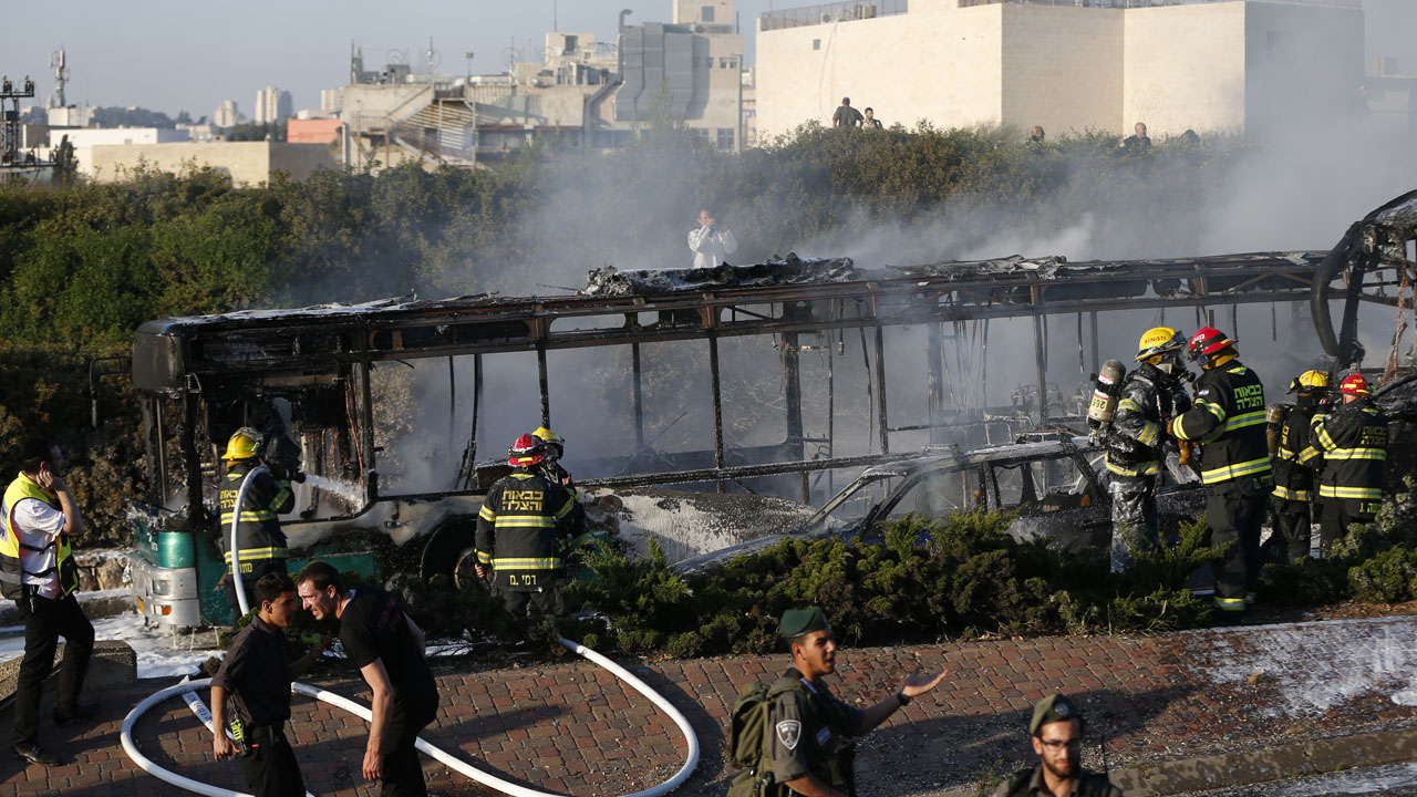 "Israeli security forces stand guard as firemen extinguish a burning bus following an attack in Jerusalem on April 18, 2016 Police only said there was ""an attack"" without providing further details. Rescue service Magen David Adom reported the explosion and at least 15 wounded, including two seriously.  / AFP PHOTO / AHMAD GHARABLI"
