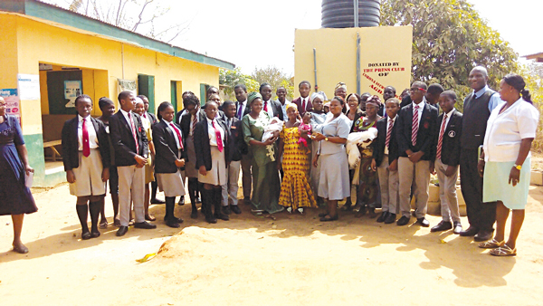 Students of Corona Secondary School, (CSS) Agbara Press Club, in a group photograph with staff of Odugbe Health/Maternity Centre, after the commissioning of the borehole facility.