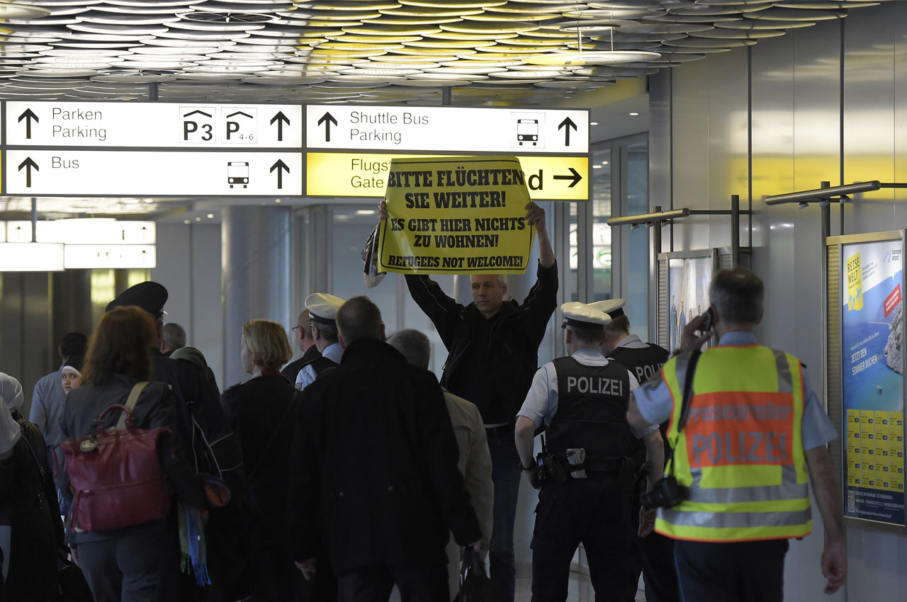 "A protester holds a banner reading ""Please keep fleeing! There is nothing to stay here! Refugees not welcome!"" as policemen escort a group of refugees after their arrival at the airport in Hanover, central Germany, on April 4, 2016. The first Syrians arrived in Germany from Istanbul under a controversial EU-Turkey migrants pact, an official from the German federal refugee office told AFP. / AFP / TOBIAS SCHWARZ"