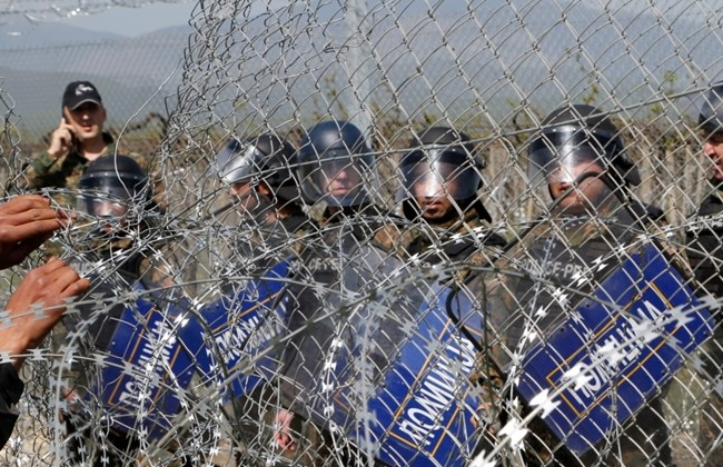 A group of migrant men attempt to tear apart the fence during a protest at the northern Greek border point of Idomeni, Greece, Sunday, April 10, 2016. (AP Photo/Amel Emric)