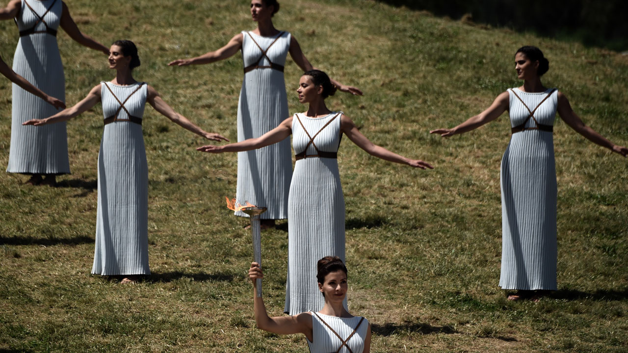 Greek actress Katerina Lechou, acting as the high priestess, holds a torch with the Olympic flame at the ancient stadium of Olympia on April 20, 2016, during a dress rehearsal of the lighting ceremony of the Olympic flame in ancient Olympia, the sanctuary where the Olympic Games were born in 776 BC. / AFP PHOTO / ARIS MESSINIS