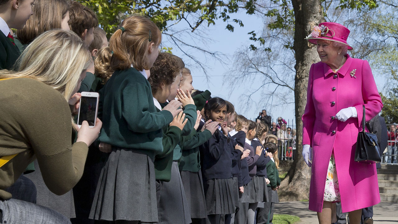Britain's Queen Elizabeth II smiles as she is greeted by school children as she arrives to open a bandstand at Alexandra Gardens in Windsor, west of London, on April 20, 2016, the day before her 90th birthday. Queen Elizabeth II is set to celebrate her 90th birthday on April 21, with a family gathering and a cake baked by a reality television star, as a new poll finds Britain's longest serving monarch is as popular as ever. The queen has reigned for more than 63 years and shows no sign of retiring, even if she has in recent years passed on some of her duties to the younger royals. / AFP PHOTO / JUSTIN TALLIS