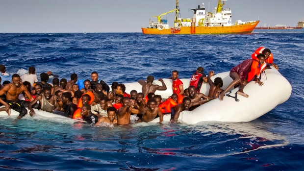 Migrants ask for help from a dinghy boat as they are approached by the SOS Mediterranee's ship Aquarius, background, off the coast of the Italian island of Lampedusa, on April 17, 2016. (Patrick Bar / SOS Mediterranee)