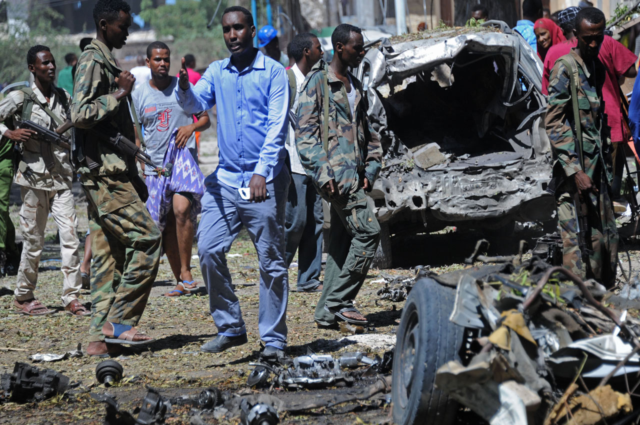 Somali soldiers stand at the scene of car bomb at Al Hindi restaurant, near government offices, in Mogadishu on April 11, 2016.  At least five people including two children were killed today in a car bomb blast outside government offices in the capital Mogadishu, a local government spokesman said. The car, which was packed with explosives, was parked in front of shops near the headquarters of the city's local government.   / AFP PHOTO / MOHAMED ABDIWAHAB