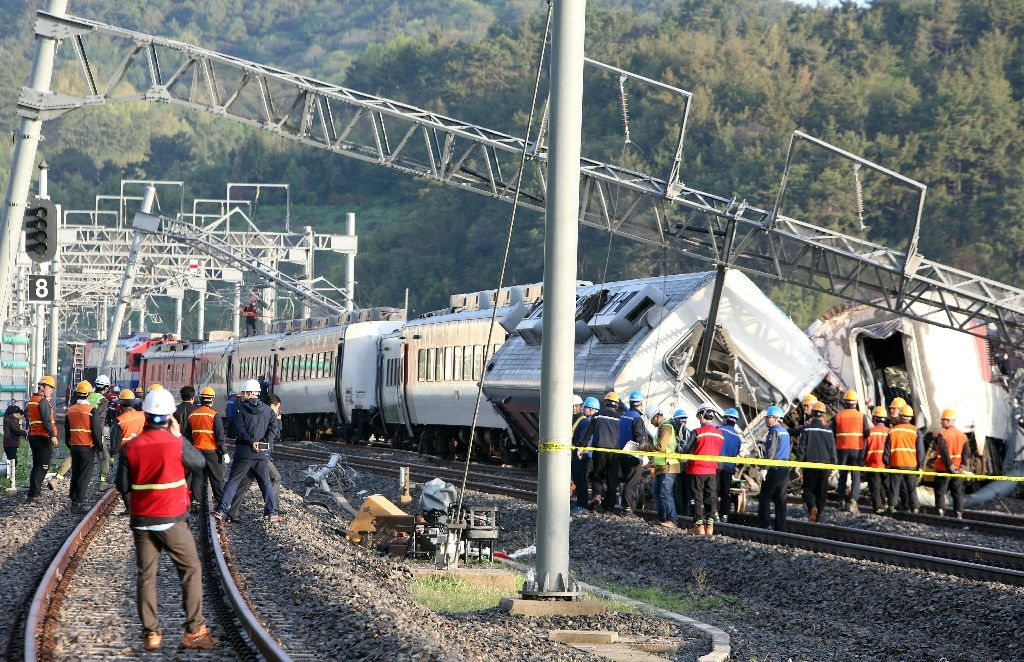 South Korea railway workers struggle to put a derailed passenger train back on track in the southern port city of Yeosu on April 22, 2016 (AFP Photo/)