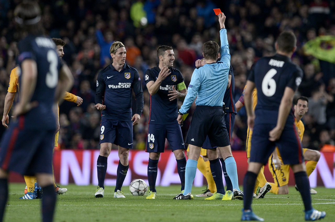German referee Felix Brych (C) shows a red card to Atletico Madrid's forward Fernando Torres (R) during the UEFA Champions League quarter finals first leg football match FC Barcelona vs Atletico de Madrid at the Camp Nou stadium in Barcelona on April 5, 2016. / AFP / JOSEP LAGO