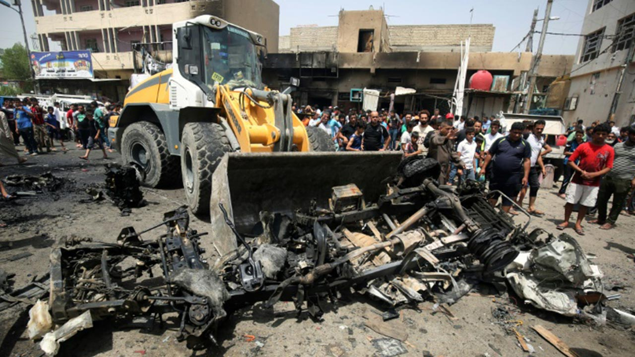 A bulldozer clears the wreckage following a car bomb attack in Sadr City, a Shiite area north of the capital Baghdad, on May 11,2016. PHOTO: AFP