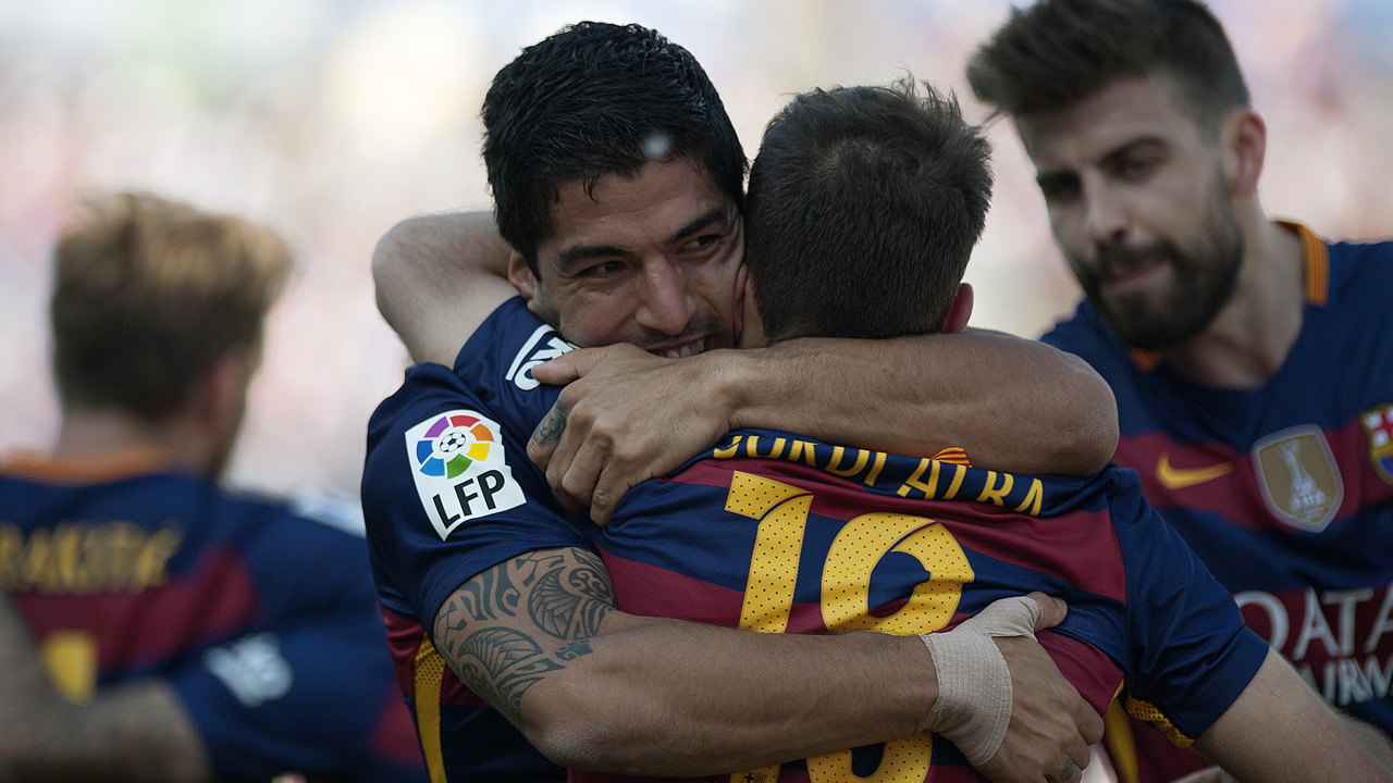 Barcelona's Uruguayan forward Luis Suarez (L) celebrates with Barcelona's defender Jordi Alba (R) after scoring during the Spanish league football match Granada FC vs FC Barcelona at Nuevo Los Carmenes stadium in Granada on May 14, 2016. Barcelona sealed their 24th La Liga title as Luis Suarez took his tally for the season to 59 goals with a hat-trick in a 3-0 win at Granada to hold off Real Madrid's late-season surge. / AFP PHOTO / JORGE GUERRERO
