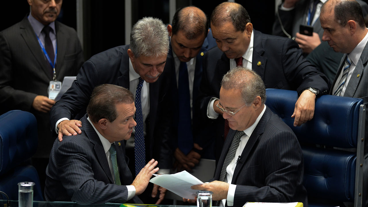 The presidnet of the Brazilian Senate Renan Calheiros (R, bottom) speaks with senators during a session to vote on Senator Delcidio do Amaral's cassation in Brasilia, on May 10, 2016.  The interim speaker of Brazil's lower house of Congress Waldir Maranhao on Tuesday said he had reversed a decision to annul the impeachment of Brazilian President Dilma Rousseff after Calheiros, on Monday had dismissed his annulment. / AFP PHOTO / ANDRESSA ANHOLETE