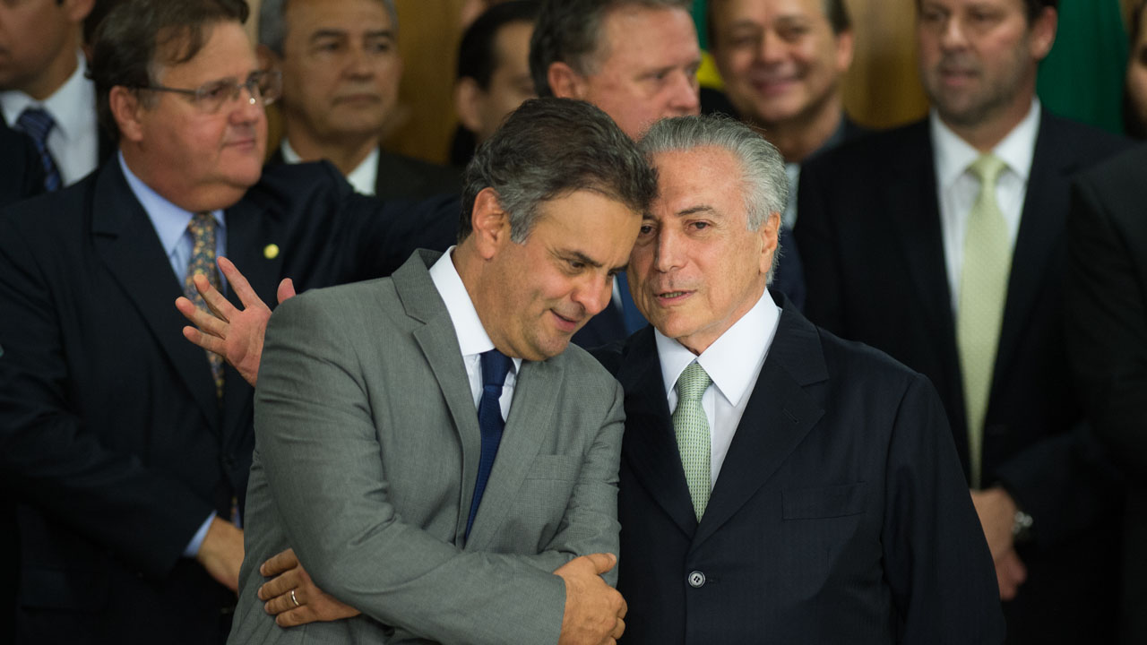 """Brazilian acting President Michel Temer (R) and Senator Aecio Neves during the new ministers inauguration ceremony at Planalto palace in Brasilia, on May 12, 2016.  Temer said Thursday his new cabinet must work to restore the country's """"credibility,"""" in his first address after assuming power from suspended predecessor Dilma Rousseff pending her impeachment trial. / AFP PHOTO / ANDRESSA ANHOLETE"""