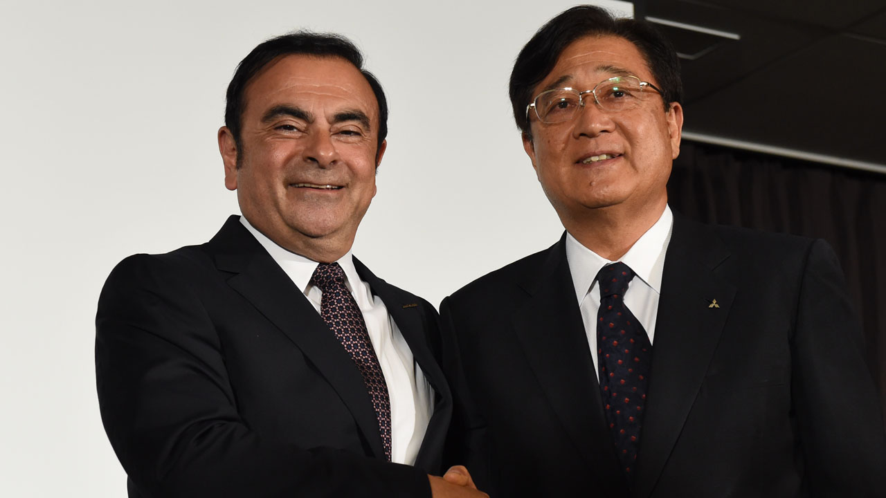 Nissan president and CEO Carlos Ghosn (L) shakes hands with Mitsubishi Motors chairman and CEO Osamu Masuko (R) at the end of their joint press conference in Yokohama on May 12, 2016. Nissan threw a lifeline to Mitsubishi Motors on May 12 by confirming plans to buy a 34 percent stake in the scandal-hit automaker, with the deal valued at about 2.2 billion USD according to a regulatory filing. / AFP PHOTO / Toshifumi KITAMURA
