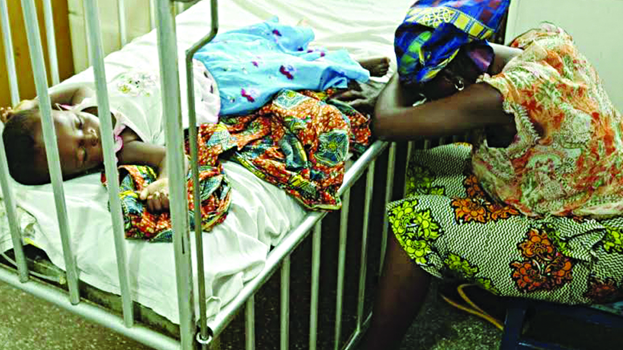 Sick child on a hospital bed under the watch of tired mother