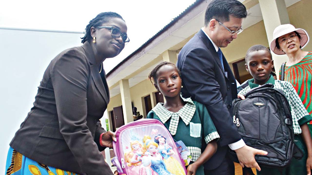 Ogun State Commissioner for Education, Mrs Modupe Mujota (left) and the Chinese Consular General in Lagos, Mr. Liu Kan, presenting school bags to pupils of the school during the commissioning of the project.