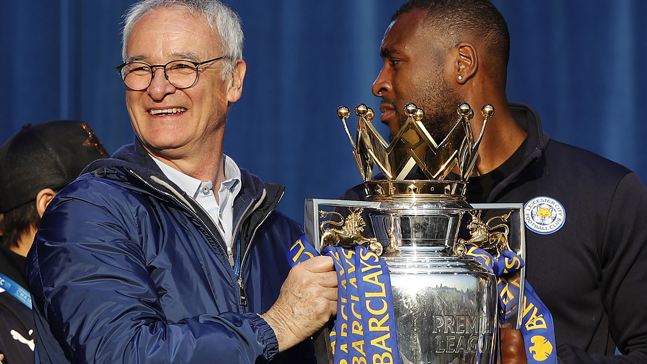 Leicester City's Italian manager Claudio Ranieri (L) and Leicester City's English defender Wes Morgan hold the Premier league trophy as the Leicester City football team celebrate in Victoria Park, after taking part in an open-top bus parade through Leicester, to celebrate winning the Premier League title on May 16, 2016. / AFP PHOTO / ADRIAN DENNIS