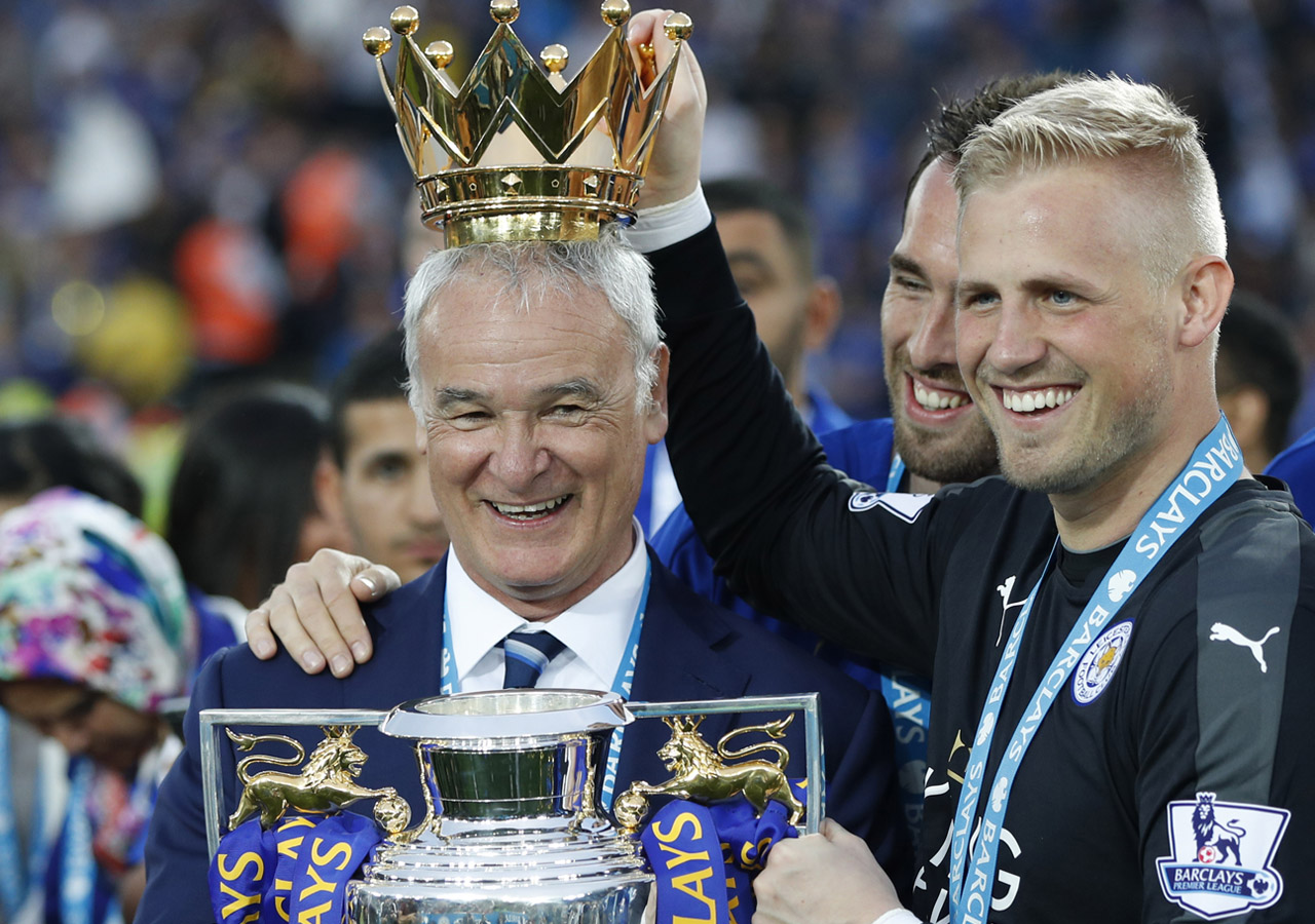 Leicester City's Italian manager Claudio Ranieri (L) poses with Leicester City's Austrian defender Christian Fuchs (C) and Leicester City's Danish goalkeeper Kasper Schmeichel with the premier league trophy after winning the league and the English Premier League football match between Leicester City and Everton at King Power Stadium in Leicester, central England on May 7, 2016. / AFP PHOTO / ADRIAN DENNIS /