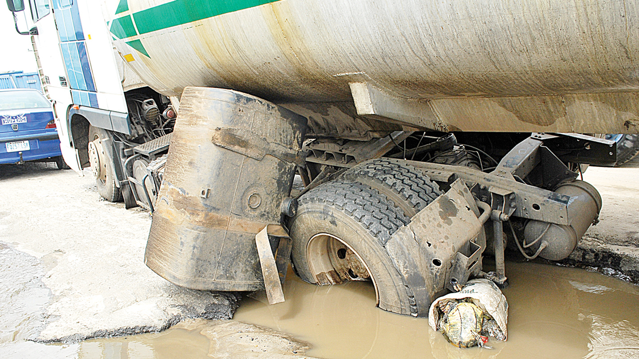 A tanker falling into a section of the deplorable road
