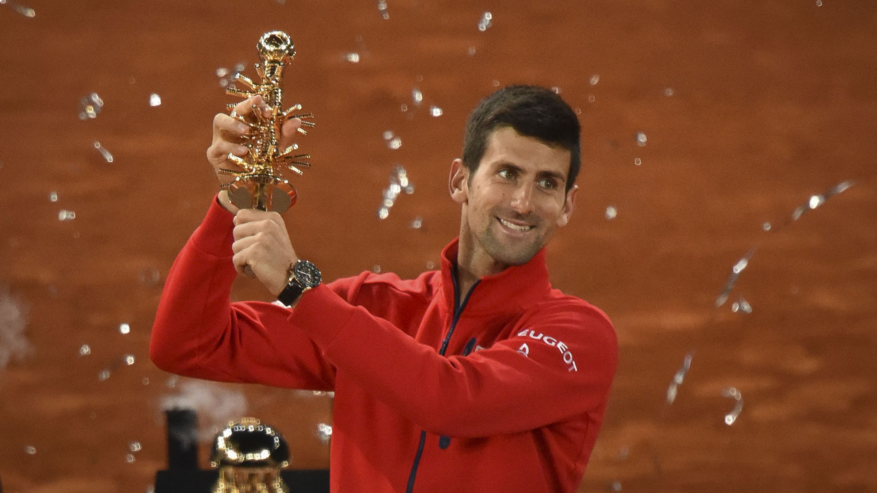 Serbia's Novak Djokovic poses with his trophy as he celebrates his victory over Britain's Andy Murray after the Madrid Open men's tennis final at the Caja Magica (Magic Box) sports complex in Madrid on May 8, 2016. / AFP PHOTO / PEDRO ARMESTRE