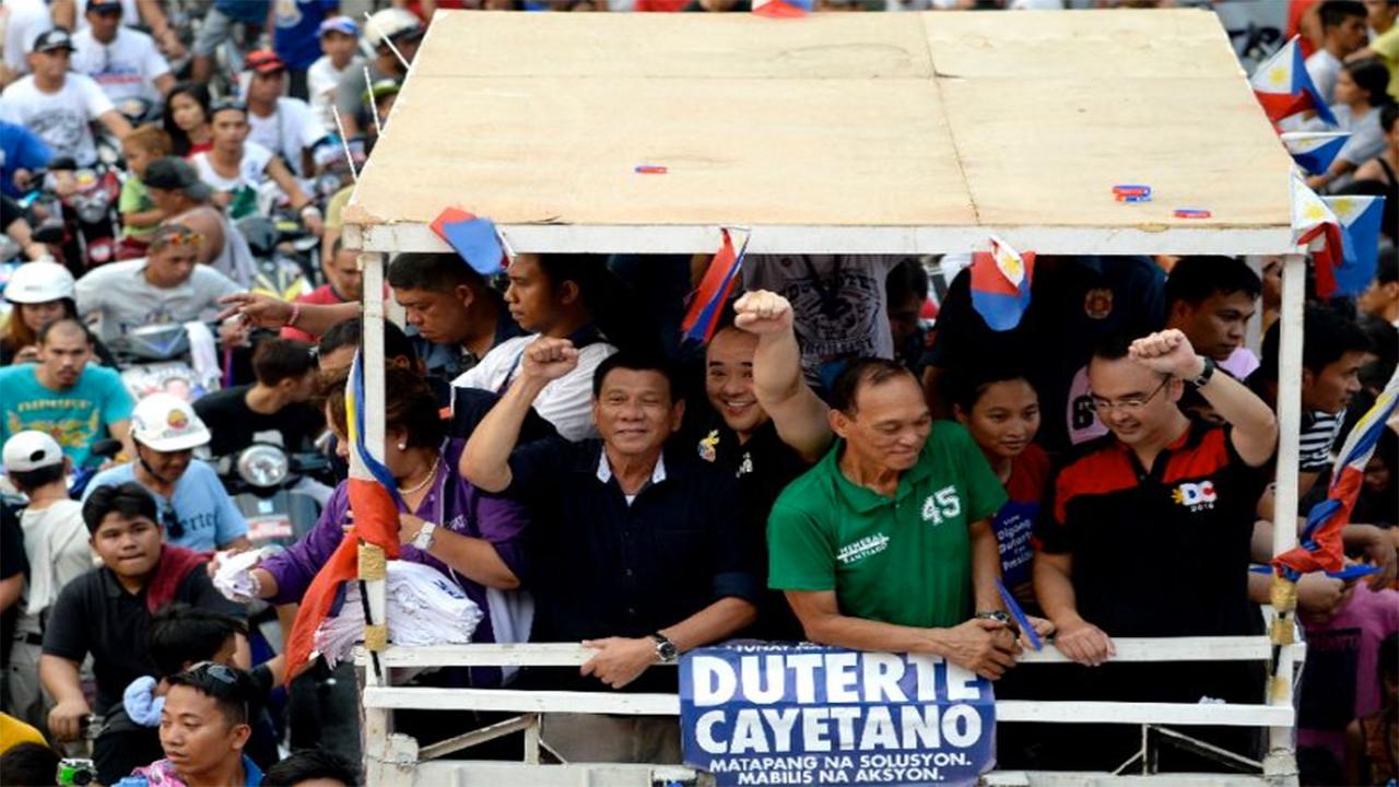 Philippine presidential candidate Rodrigo Duterte (centre L, in black) gestures to the crowd