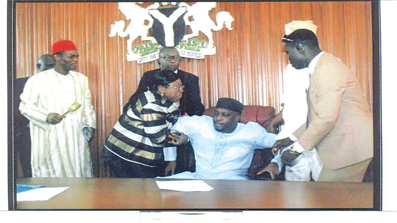 Ativie (left) pulling the former Speaker, Edoror from the seat.