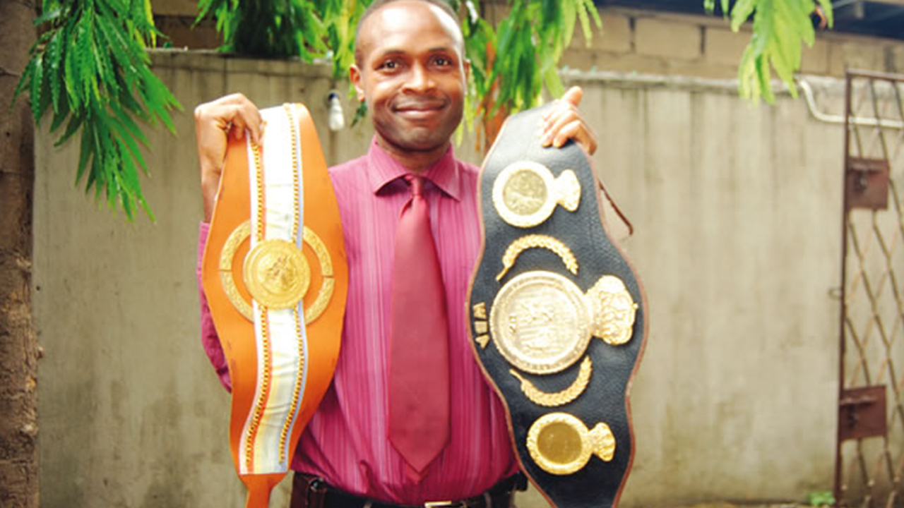 Displaying his British and Commonwealth boxing champions and WBA light heavyweight belt.