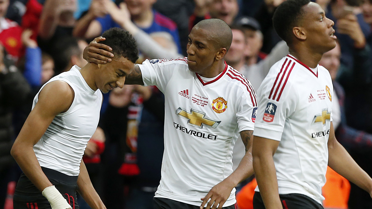 Manchester United's English midfielder Jesse Lingard (L) celebrates with Manchester United's English midfielder Ashley Young after scoring their second goal in extra time during the English FA Cup final football match between Crystal Palace and Manchester United at Wembley stadium in London on May 21, 2016. / AFP PHOTO / IAN KINGTON