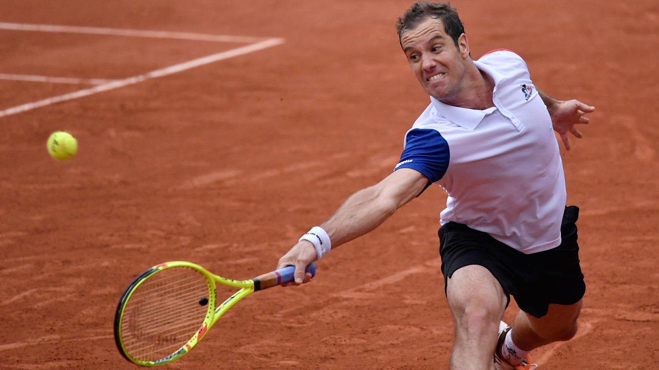 Richard Gasquet stretches to return the ball to Kei Nishikori during their men's fourth round match at the French Open in Paris…on Sunday. PHOTO: AFP.