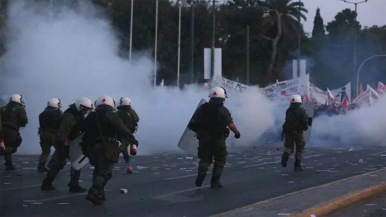 Riot police disperse demonstrators during minor clashes that broke out during a protest against reforms to the tax and pension system