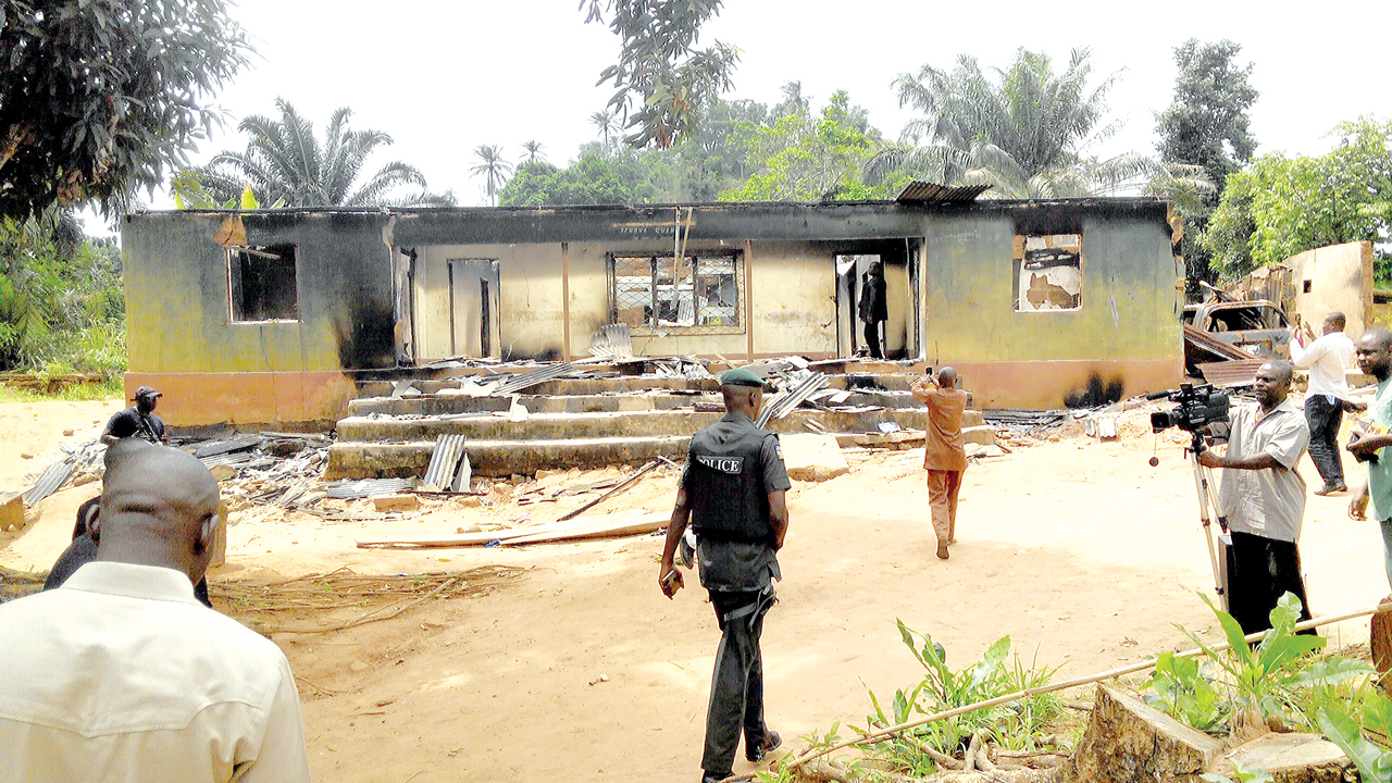 A burnt building (Inset: a victim being conveyed to a hospital (left); another victim in a ward)  PHOTOS: LAWRENCE NJOKU