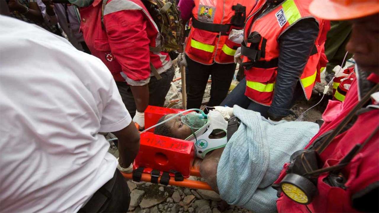 A woman is carried on a stretcher by medical personnel after she was rescued alive, six days after being trapped in the rubble of a house that collapsed in Kenya.