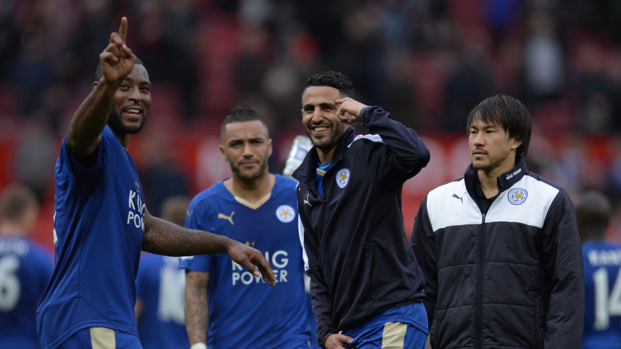Leicester City's English defender Wes Morgan (L) and Leicester City's Algerian midfielder Riyad Mahrez (C) gesture after the English Premier League football match between Manchester United and Leicester City at Old Trafford in Manchester, north west England, on May 1, 2016. / AFP PHOTO / OLI SCARFF /