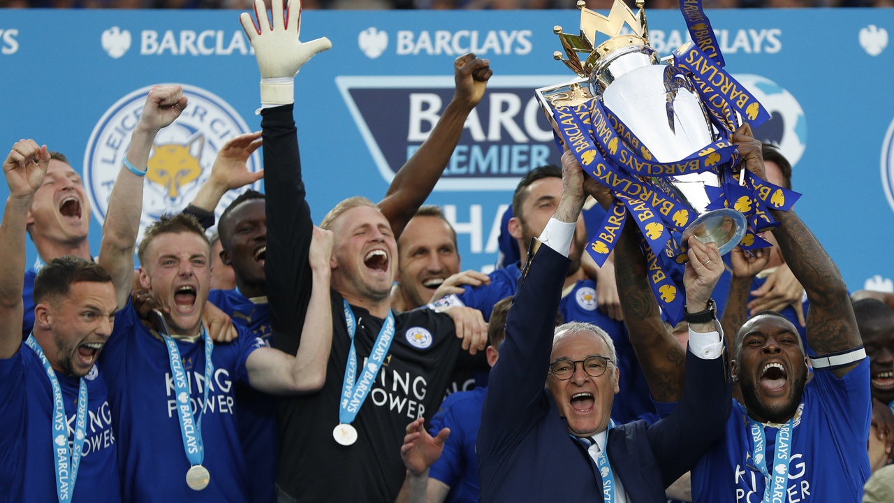 Leicester City's Italian manager Claudio Ranieri (2R) and Leicester City's English defender Wes Morgan hold up the Premier league trophy after winning the English Premier League football match between Leicester City and Everton at King Power Stadium in Leicester, central England on May 7, 2016. / AFP PHOTO / ADRIAN DENNIS