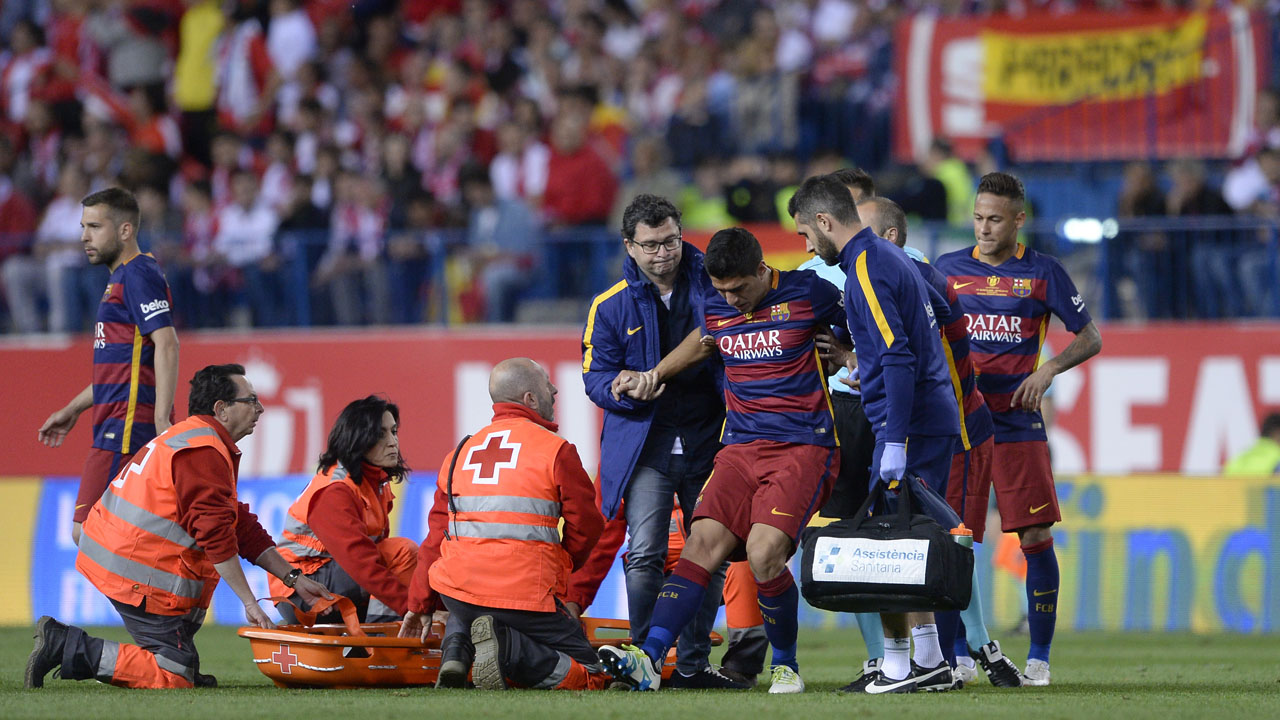 """Barcelona's Uruguayan forward Luis Suarez (C) is assited after being injured beside Barcelona's Argentinian forward Lionel Messi during the Spanish """"Copa del Rey"""" (King's Cup) final match FC Barcelona vs Sevilla FC at the Vicente Calderon stadium in Madrid on May 22, 2016. / AFP PHOTO / JOSEP LAGO"""