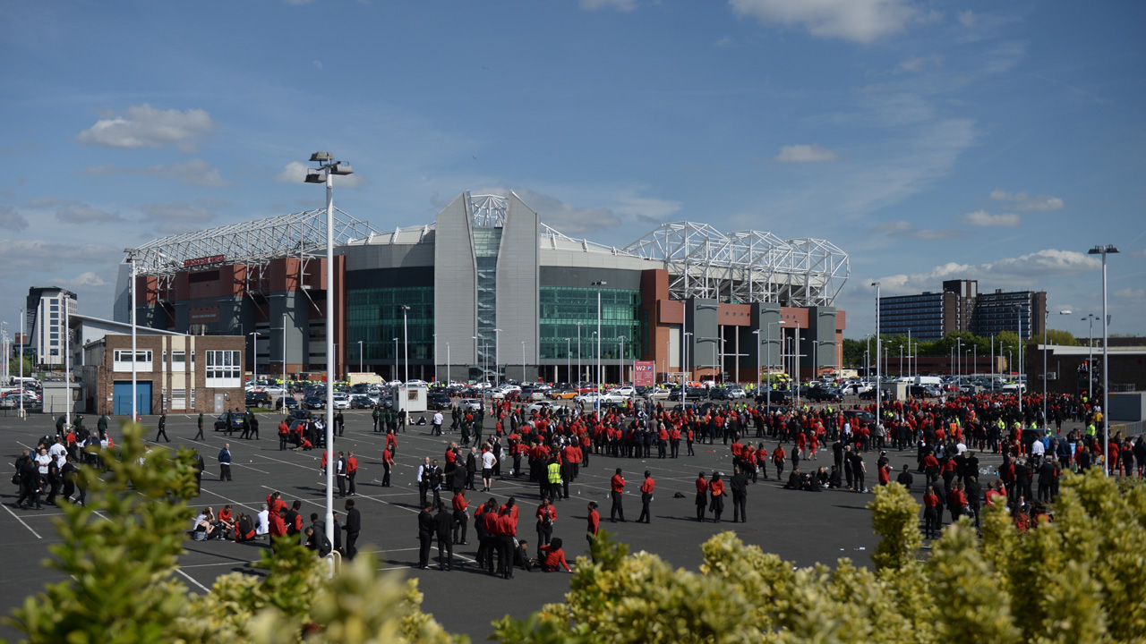 Old Trafford stadium workers stand in a car park outside the stadium in Manchester, north west England, on May 15, 2016, after the English Premier League football match between Manchester United and Bournemouth was abandoned. Police ordered Manchester United to abandon their final Premier League game of the season against Bournemouth on Sunday after a suspicious package was discovered at Old Trafford. OLI SCARFF / AFP