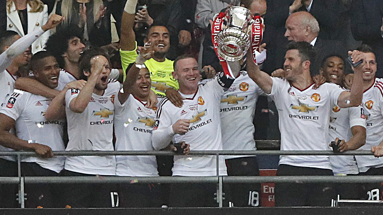Manchester United's English striker Wayne Rooney (centre left) and Manchester United's English midfielder Michael Carrick lift the trophy as players celebrate their victory after extra time in the English FA Cup final football match between Crystal Palace and Manchester United at Wembley stadium in London on May 21, 2016. Manchester United won the game 2-1, after extra time. / AFP PHOTO / Adrian DENNIS