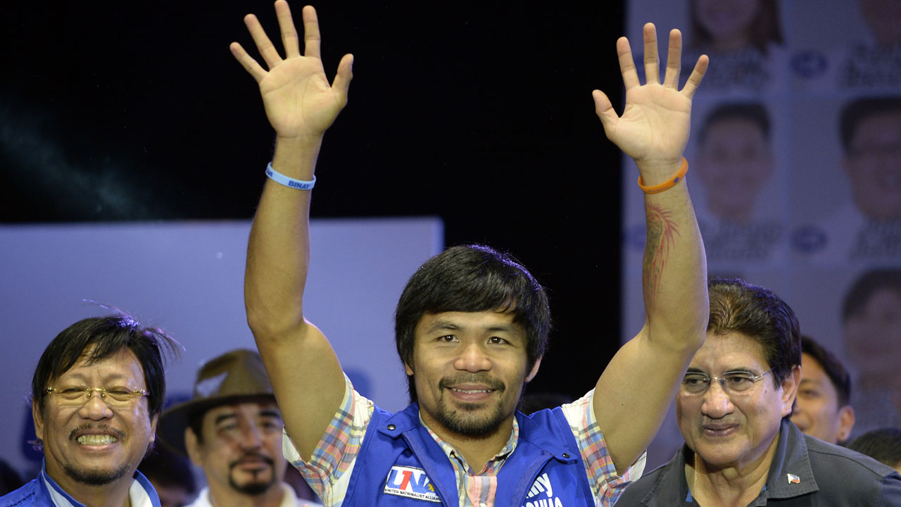 Philippine boxing champion and senatorial candidate Manny Pacquiao speaks onstage during presidential candidate and Vice President Jejomar Binay's Miting De Avance in Manila on May 7, 2016.  Philippine President Benigno Aquino warned May 7 the frontrunner in the race to replace him carried similar dangers to Hitler and would bring terror to the nation. / AFP PHOTO / NOEL CELIS
